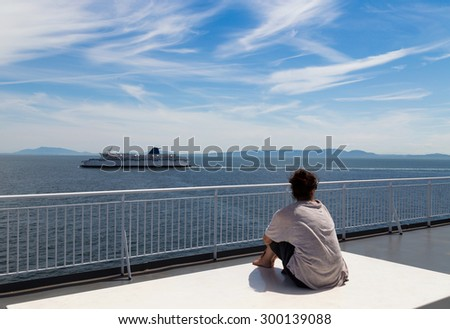 Woman sitting on a ship deck looking out onto the sea