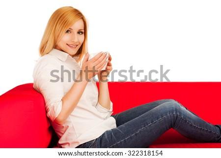 Woman sitting on a sofa drinking coffee. - stock photo