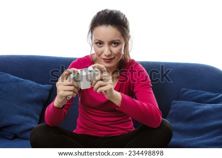 woman sitting on a sofa playing a game on a games consoles controller - stock photo