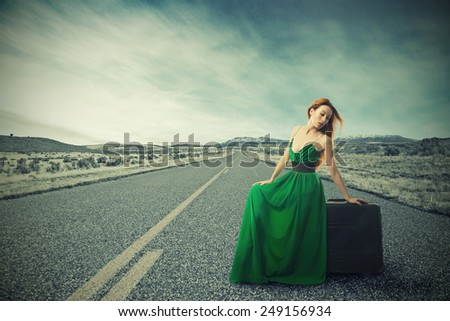 Woman sitting on a suitcase on a countryside road waiting for a ride  - stock photo