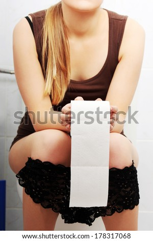 Woman sitting on a toilet holding toilet paper. Stomach issues concept.  - stock photo