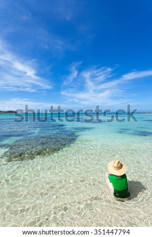Woman sitting on a tropical beach with shallow clear water, Amami Oshima Island, Japan - stock photo