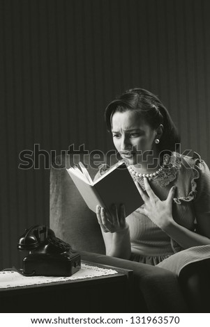 Woman sitting on armchair, reading a horror novel