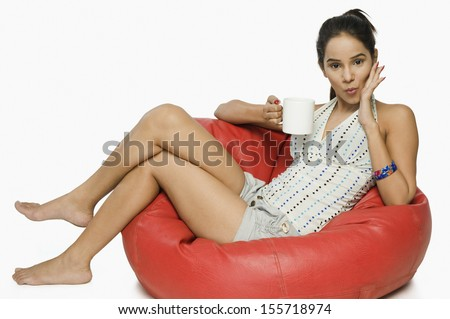 Woman sitting on bean bag with cup of coffee - stock photo