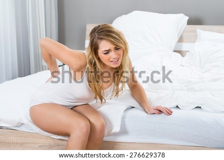 Woman Sitting On Bed Suffering From Back Pain - stock photo