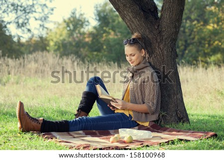 woman sitting on bedding on green grass with a book during picnic in the park - stock photo
