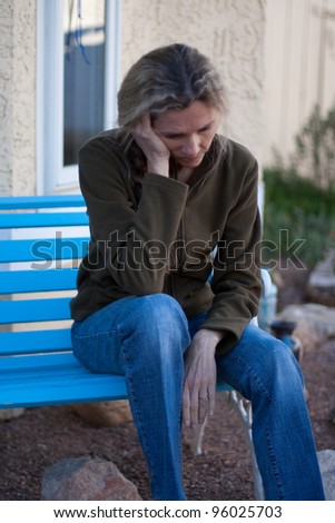 Woman sitting on bench depressed and frustrated