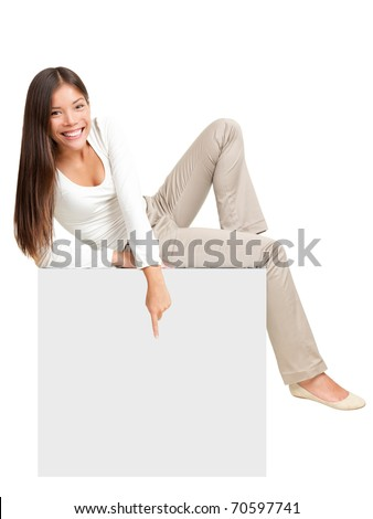 Woman sitting on blank empty paper poster, pointing down at copy space. Whole body image of cute casual woman in white isolated on white background. - stock photo