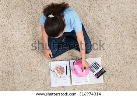 Woman Sitting On Carpet With Invoices And Money Inserting Coin In Piggybank - stock photo