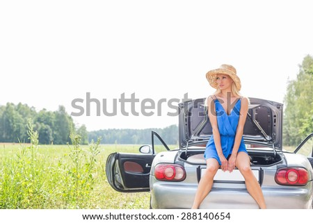Woman sitting on convertible trunk against clear sky