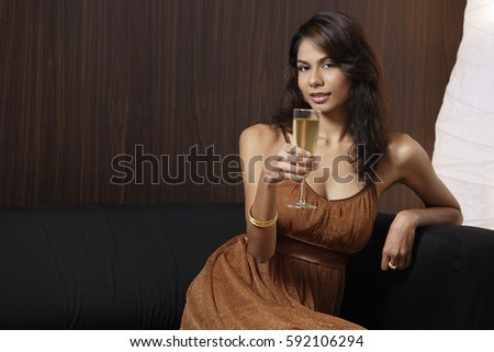 Woman sitting on couch, holding champagne glass, smiling at camera
