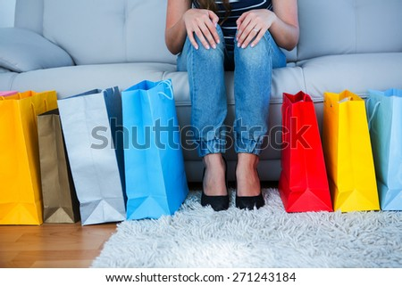 Woman sitting on couch with shopping bags at home in the living room