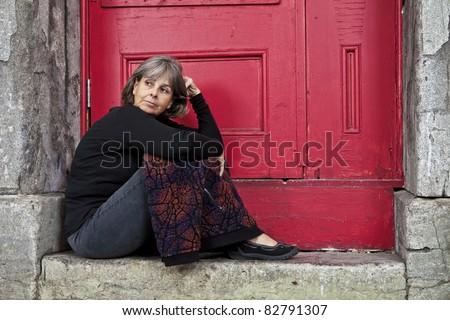 Woman sitting on door stoop - stock photo