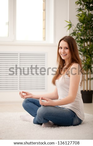 Woman sitting on floor at home doing yoga meditation
