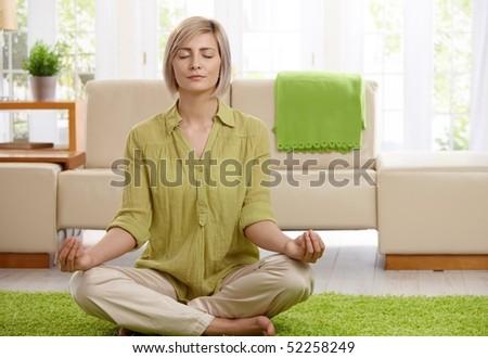 Woman sitting on floor at home doing yoga meditation. - stock photo