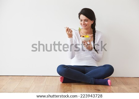 Woman Sitting On Floor Eating Bowl Of Fresh Fruit - stock photo