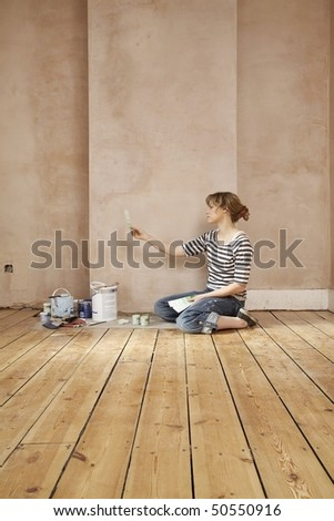 Woman sitting on floor of unrenovated room, looking at colour paint swatches