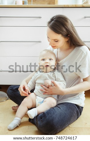 Woman sitting on floor with little baby on her arms