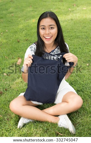 Woman sitting on grass and holding bag