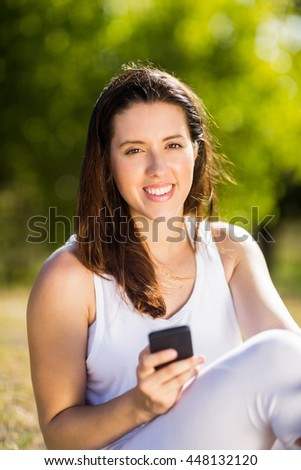 Woman sitting on grass and using mobile phone on a sunny day