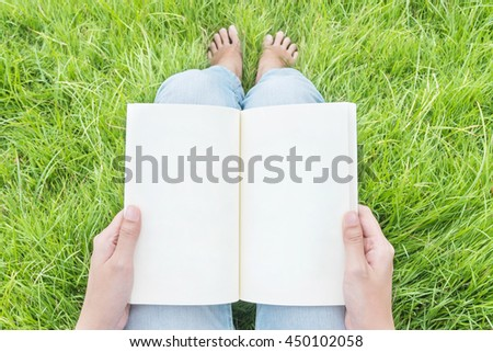 Woman sitting on grass field in the public garden for reading in the morning , relax time of asian woman