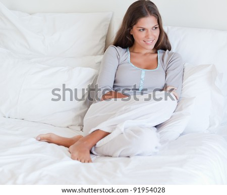 Woman sitting on her bed while looking away from the camera - stock photo