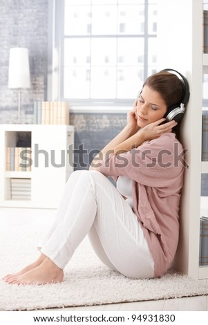 Woman sitting on living room floor with headphones, listening to music with eyes closed, smiling.? - stock photo