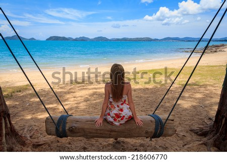 Woman Sitting On Log Swing On The Beach