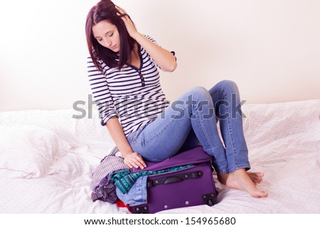 Woman sitting on luggage to close it. - stock photo