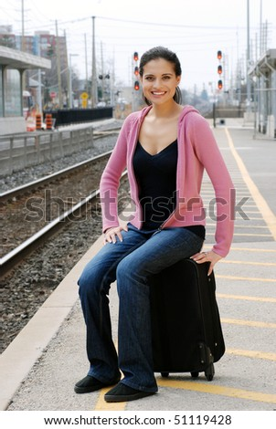 woman sitting on luggage waiting for train - stock photo