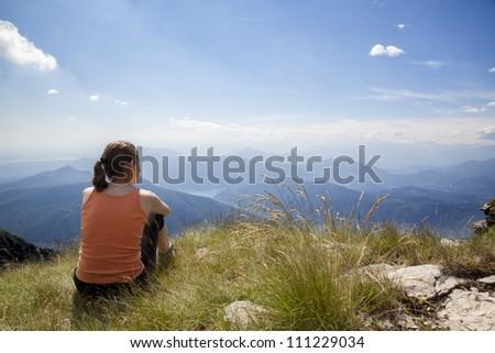Woman sitting on mountain top of Monte Generoso admiring mountain landscape around Lugano lake and blue sky. - stock photo