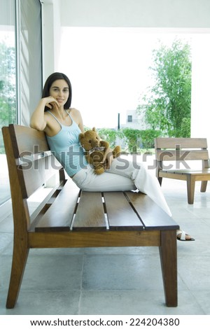 Woman sitting on patio furniture holding teddy bear, full length