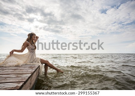 woman sitting on pier at sunrise