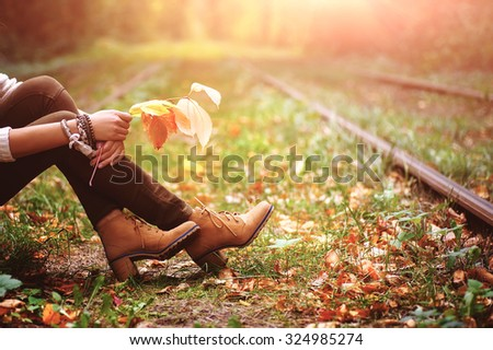 woman sitting on rail trails and holding colorful autumn leaves.  natural vintage background - stock photo