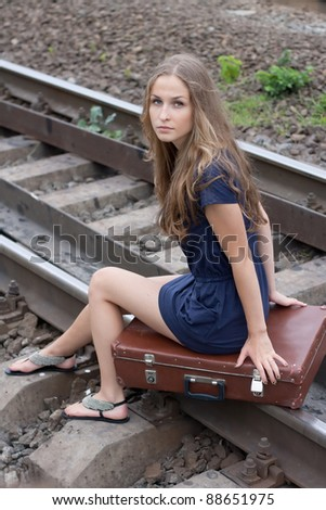 Woman sitting on rails outdoors shooting