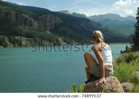 Woman sitting on rock by lake