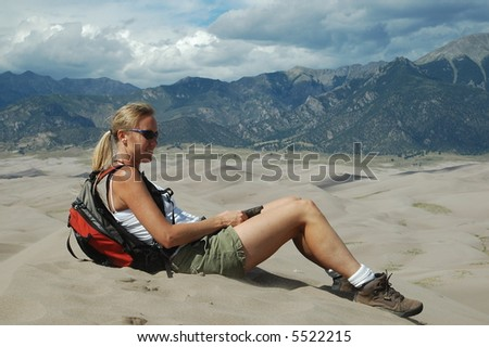 Woman sitting on sand dune