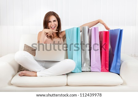Woman Sitting On Sofa Holding Shopping Bag At Home. - stock photo
