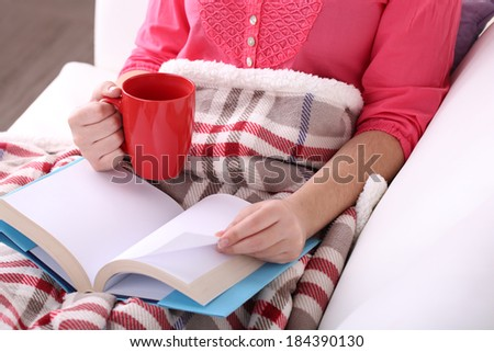 Woman sitting on sofa,  reading book and  drink coffee or tea, close-up - stock photo