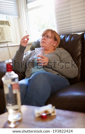 Woman Sitting On Sofa With Bottle Of Vodka And Cigarettes