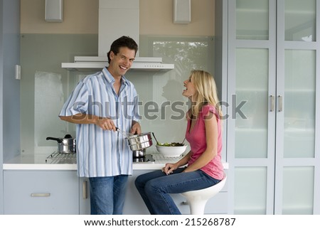 Woman sitting on stool at kitchen breakfast bar, man whisking food in pan, smiling, side view