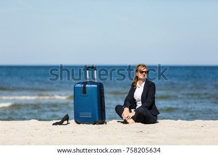 Woman sitting on suitcase on beach