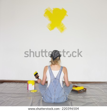 Woman sitting on tarp with paintbrush and paint - stock photo