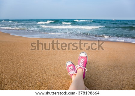 Woman sitting on the beach with first person perspective view, legs in focus - stock photo