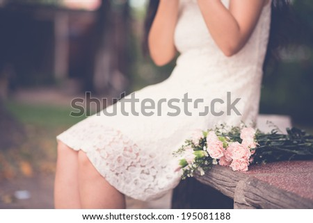 Woman sitting on the bench with bouquet of flowers