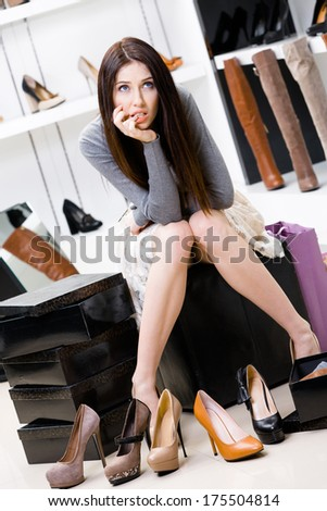 Woman sitting on the chair and trying on footwear in the shop can't decide what to buy - stock photo