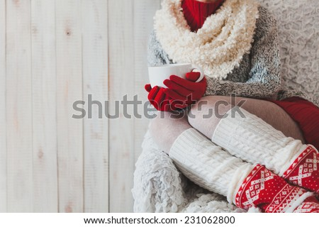 Woman sitting on the chair in light room with cup of coffee in hands in christmas,  - stock photo