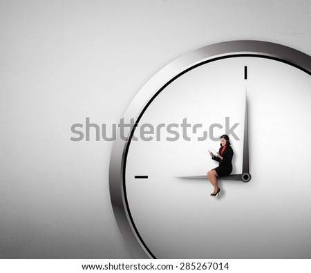 Woman sitting on the clock using tablet. Overtime conceptual - stock photo