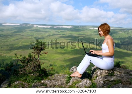 woman sitting on the edge of a cliff with a laptop - stock photo
