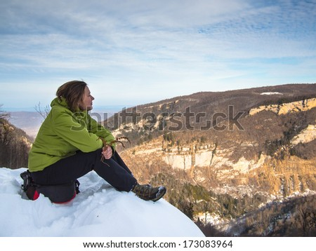 Woman sitting on the edge of the cliff on the background of mountains - stock photo